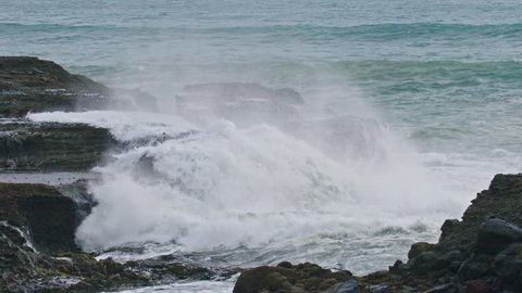 Waves crashing against rocks in slow motion at piha, auckland