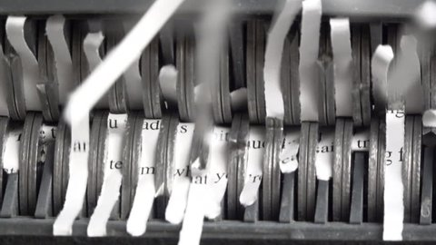 Slow motion, Extreme close up of document passing through sharp blades, cut into strips by office paper shredder. 1080p