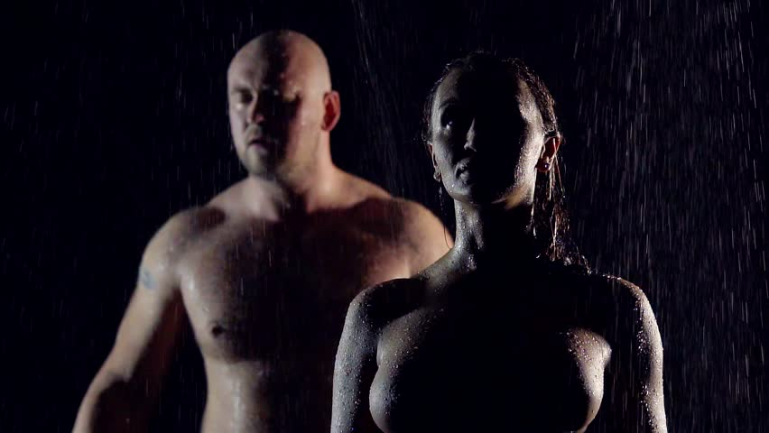Nude couple standing in the rain. beautiful girl with big Breasts in the foreground and a male athlete on the back.