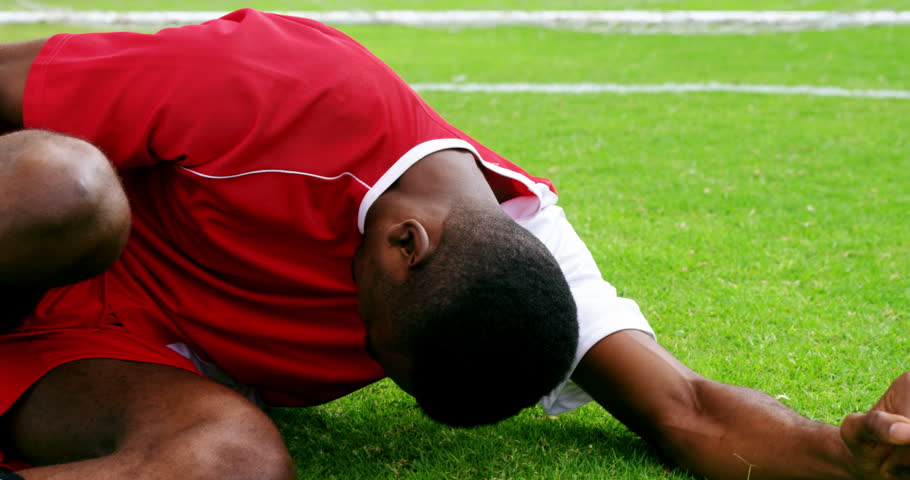 Injured football player lying on grass in the field