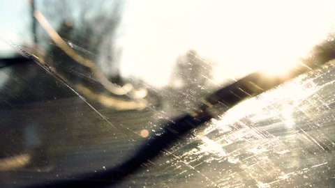 Fluid spraying on a windshield and wipers cleaning it off, in slow motion