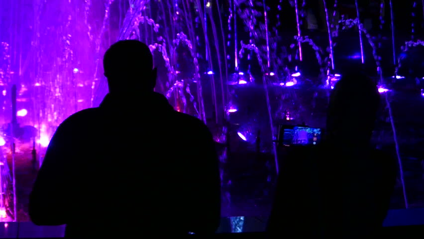 Well Illuminated and Colorful Fountain With High and Crystal Looking Streams of Water, and a Couple Looking at it With Admiration at Night.  | Shutterstock HD Video #28856431
