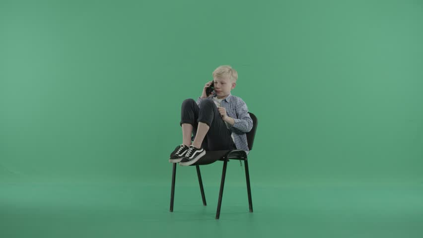 Boy sits with legs up on a chair speaking on his smartphone | Shutterstock HD Video #28857841