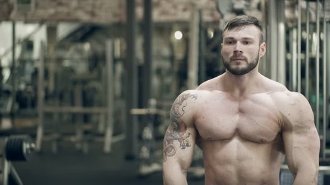 A bodybuilder with a tattoo makes a pose with a double bicep in front. The athlete with a beard performs a mandatory classic element of posing in bodybuilding. The arms and legs are tense.