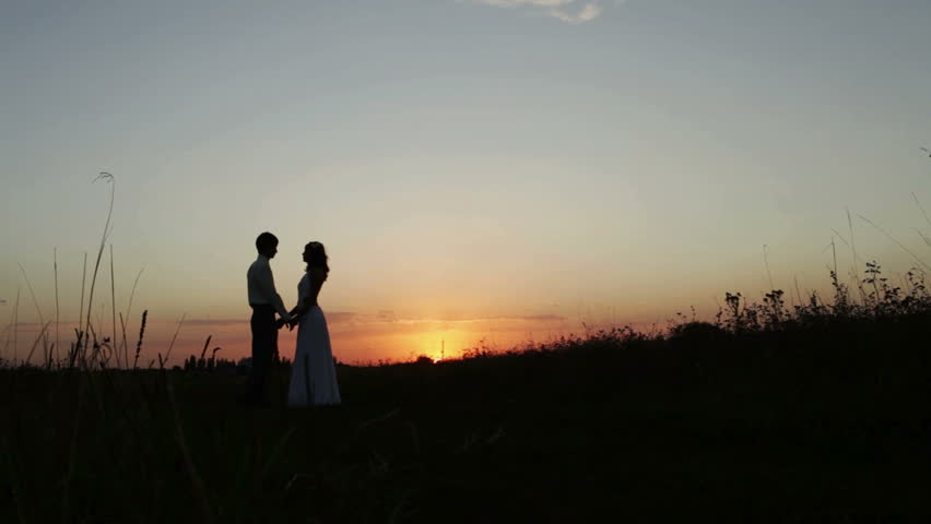 Silhouettes of lovers at sunset. Couple in love long kisses and hugs. Taken by the hand and went off