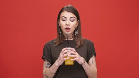 Young pretty girl drinking orange juice with bad taste isolated over red background