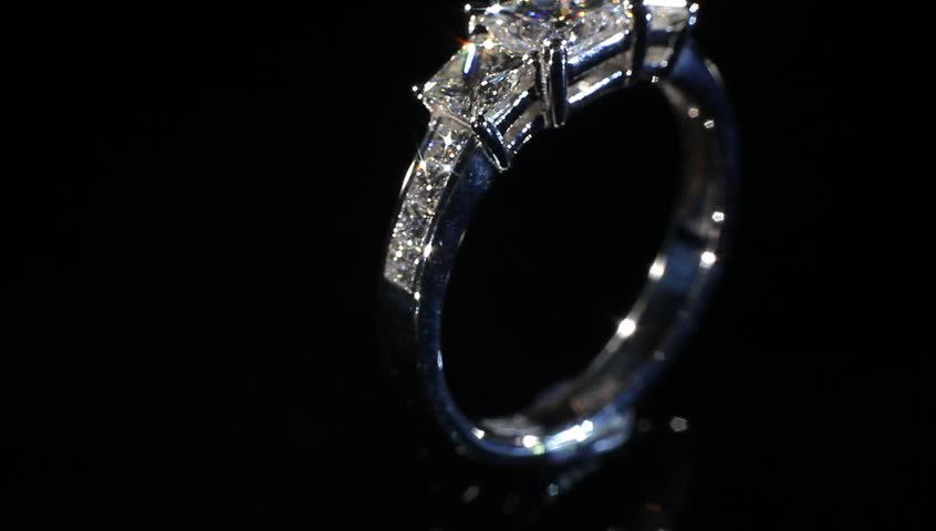 Excellence silver diamond ring turning on themselves against a black background