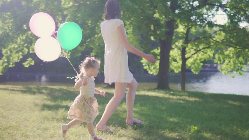 Mom and daughter are runing to the river with balloons