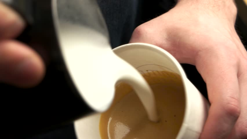 Hands make latte. Milk pouring into paper cup.