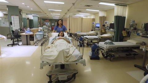 A nurse pushes a happy patient on a