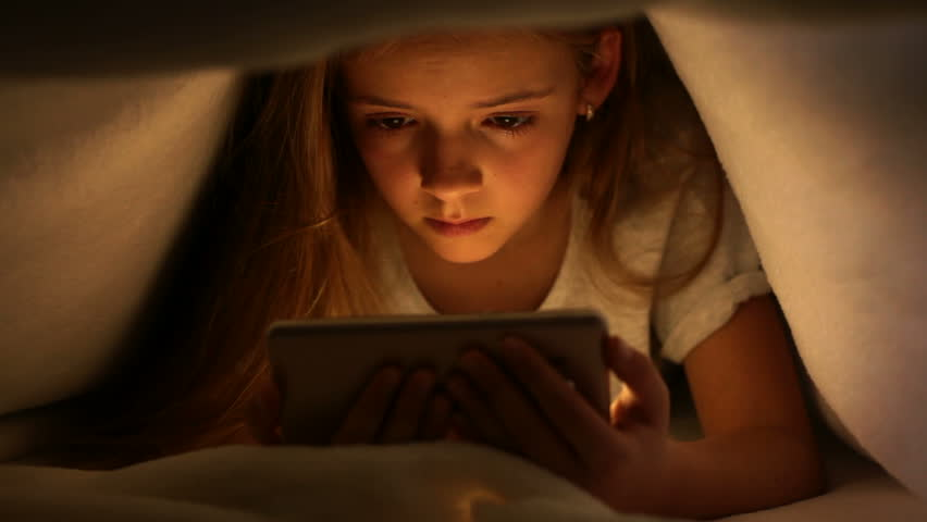 Young girl watching online content on her smartphone at night - hiding under the blanket, static camera