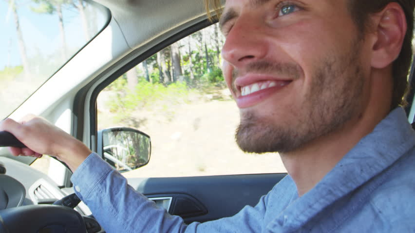 Young smiling man driving a car on a road trip