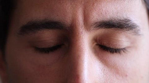 Man meditates with eyes closed then opens again with a serious look