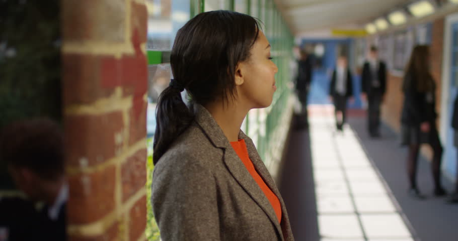 4K Portrait confident female teacher in school hallway with students chatting in background. Slow motion | Shutterstock HD Video #28960291