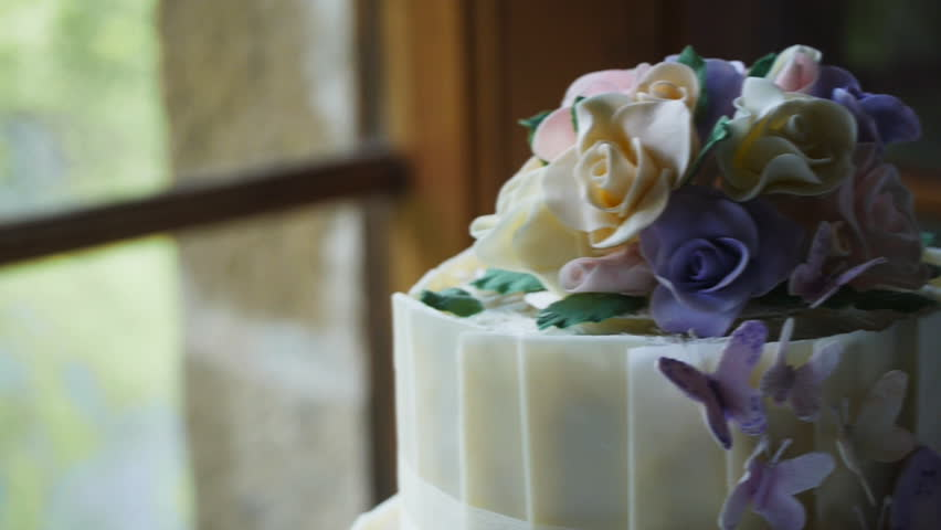 a close up dolly shot of a beautifully decorated wedding cake