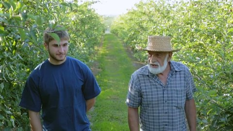 Grandfather and grandson are engaged in gardening together. Family business