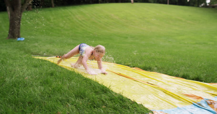 A cinematic handheld/gimbal/stabilizer/tracking/dolly shot of kids playing and an adult man having fun on a water slip and slide during a hot summer day.