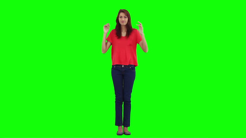 A young woman is dancing and having fun in front of a green background