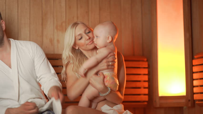 Young parents with two sons in the thermal zone bask in the sauna. A young married couple with two children - a boy of 5 years and a one-year-old baby - sit in a sauna and have a good time together
