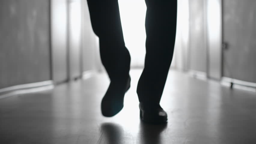 Dolly with low-section of silhouette of legs of man walking along hallway in slow motion; black and white shot