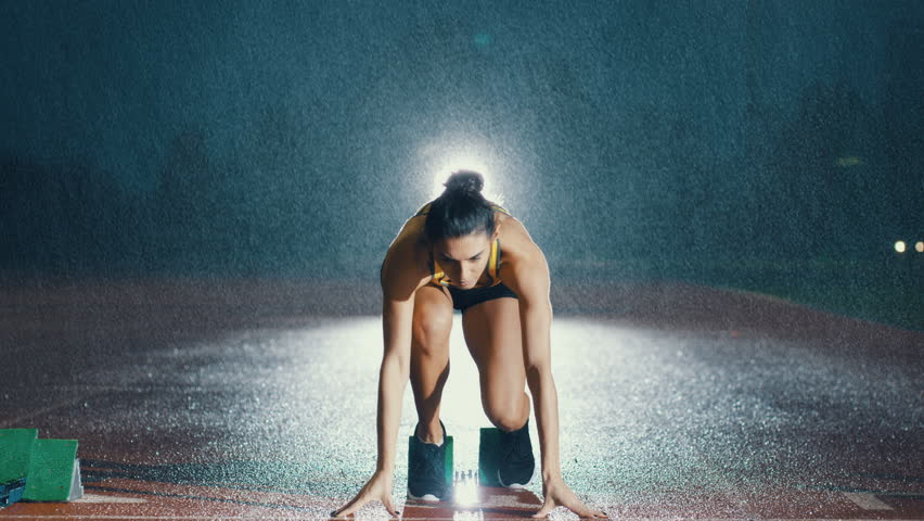 Female hispanic athlete training at running track in the dark & in the rain. Slow motion. | Shutterstock HD Video #29016901