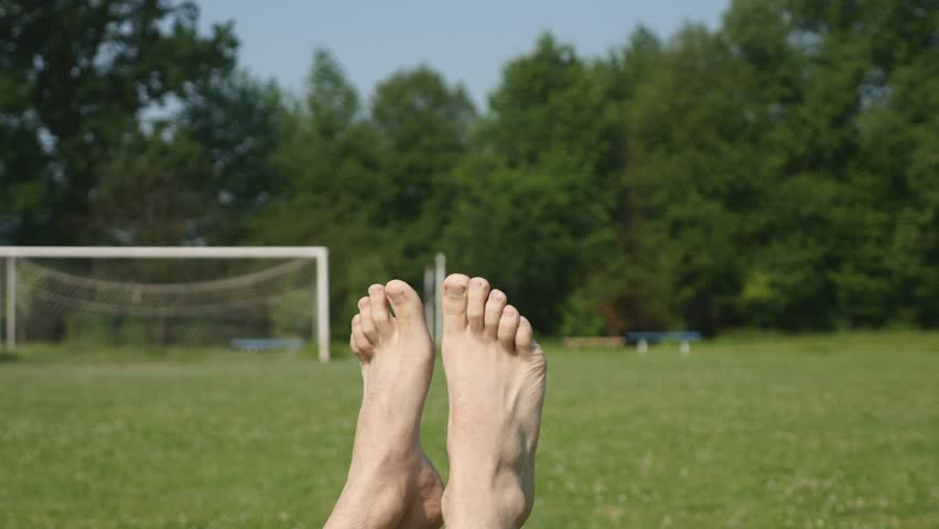 bdd934c058bb Man s feet at a trees and grass background. A happy person relaxing and  having a sun bath.