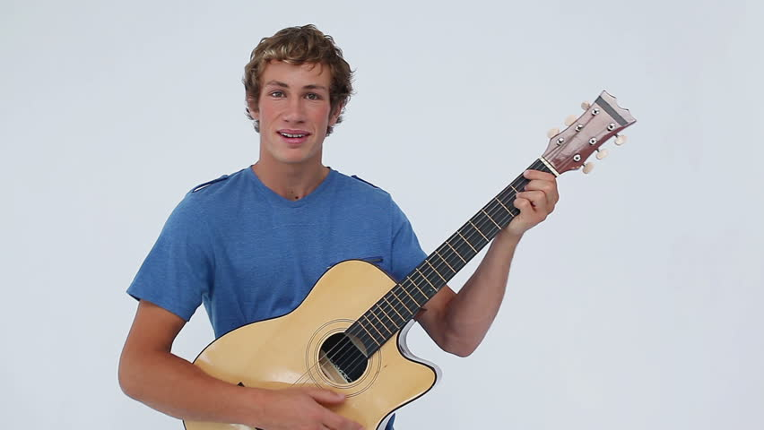 Smiling Brunette Man Playing The Guitar Against A White Background