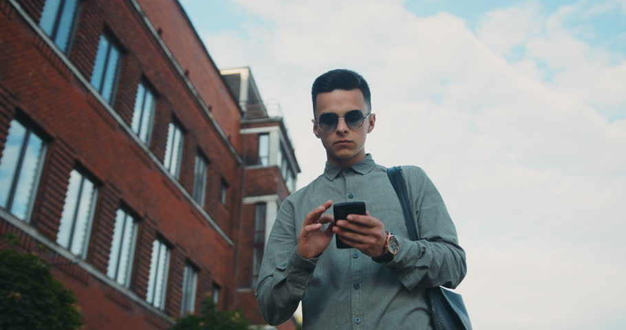 Young stylish boy guy man walking using phone street texting tapping smart casual clothing shirt city looking around blue sky sunny sunlight sunglasses elegant trendy perfect look checking news watch | Shutterstock HD Video #29050408