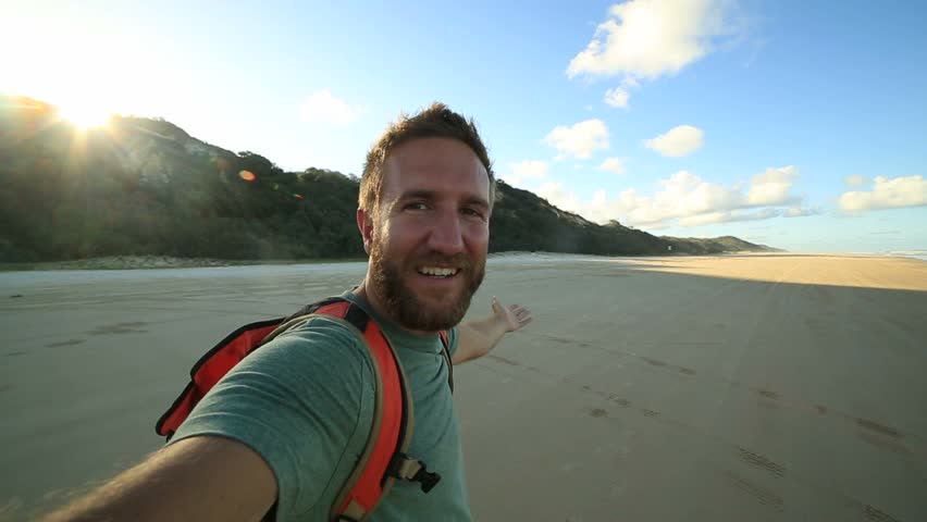 Bearded young man traveling takes selfie portrait Cheerful young man on the beach takes a selfie portrait at sunset.