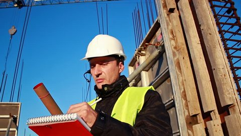 Construction supervisor;builder oversees the construction works and talk to the workers on the intercom,video clip