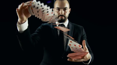 Magician in a Black Suit Steps into the Light does Card Trick Throwing Deck From one Hand to Another. Background is Dark Black. Shot on RED EPIC-W 8K Helium Cinema Camera.