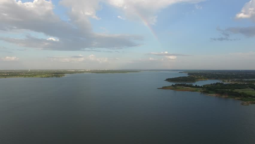 Aerial flight over Grapevine Lake with rainbow in the clouds. | Shutterstock HD Video #29118391
