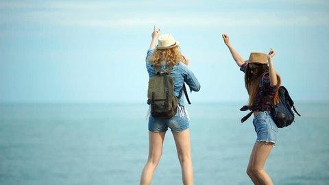 Young women enjoying and dancing on a sea shore.