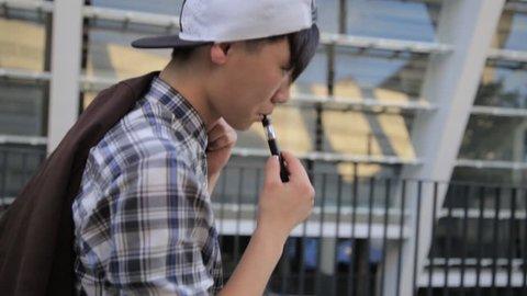 Young Man Walking On The Street And Smoke E-Cigarette. Vape.