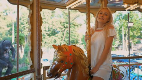 Close up of beautiful happy blonde woman having fun riding carousel in amusement park, smiling and waving at camera, graded. Slow motion.