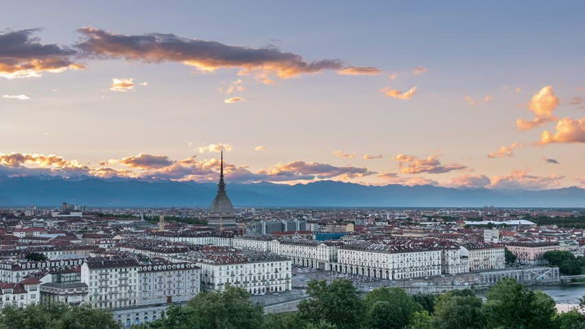 Turin time lapse, Torino skyline, Italy. Mole Antonelliana towering over the buildings. Timelapse fading from sunset to dusk, turning on city lights. Motion clouds over the Alps. Sliding version. | Shutterstock HD Video #29136961