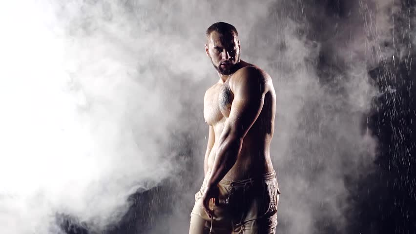 beautiful muscular young male bodybuilder posing under the jets of water against the background of fog