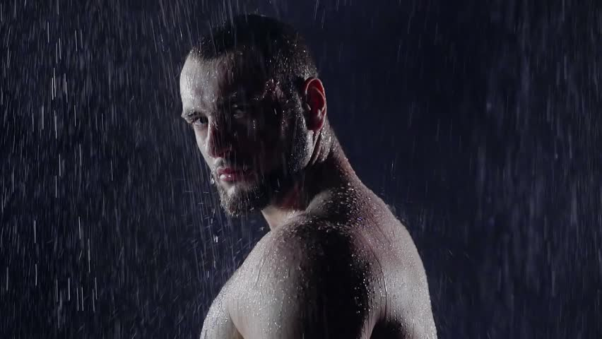 portrait of strict men under the jets of water in a dark room. he furrowed his brow and cruel looking at the camera. close-up
