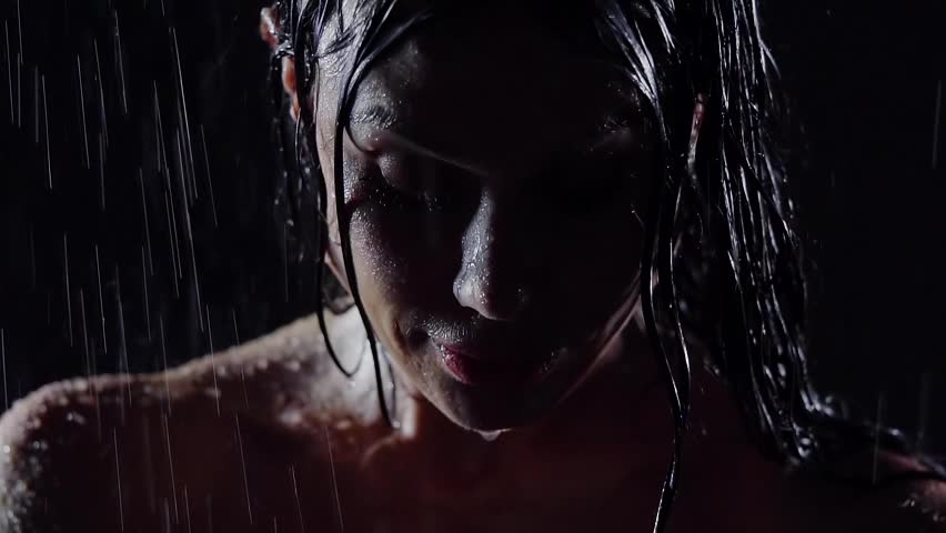 close-up. portrait of sexy girl with great cheekbones. piercing glance. silhouette face under the jets falling from the ceiling of water