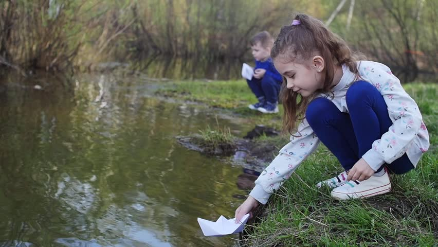 Boy and girl play with paper boats in puddle at cloudy day | Shutterstock HD Video #29187754