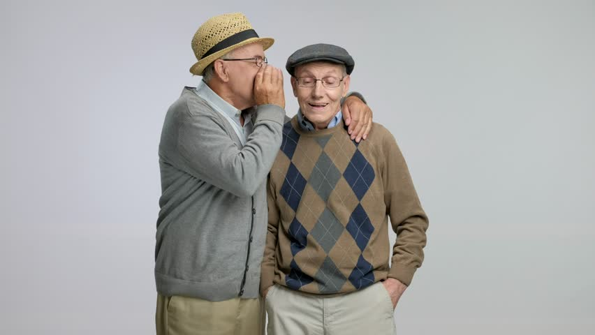 Senior whispering something funny to another senior isolated on gray background. | Shutterstock HD Video #29193571