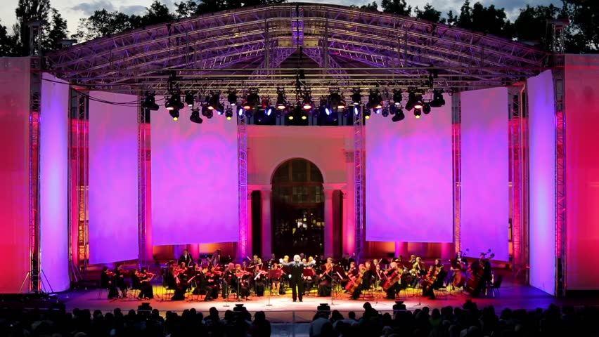 Symphony orchestra performing outdoors at open public event at night. Night scene, illuminated stage.