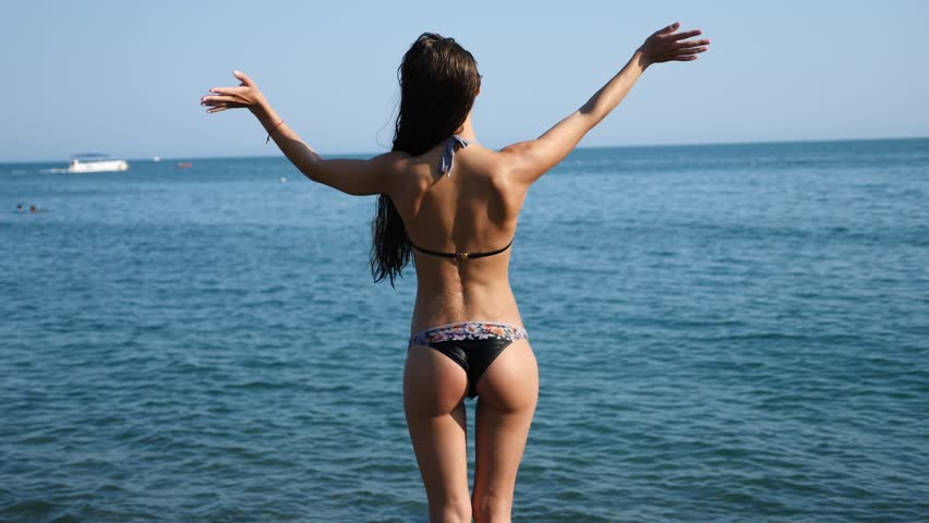 A sexy girl in a bikini splashes in the sea, standing with her back to the camera, her slim figure and elastic buttocks are visible. Slow motion, 4k.