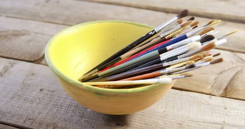 Various paintbrush arranged in bowl on table