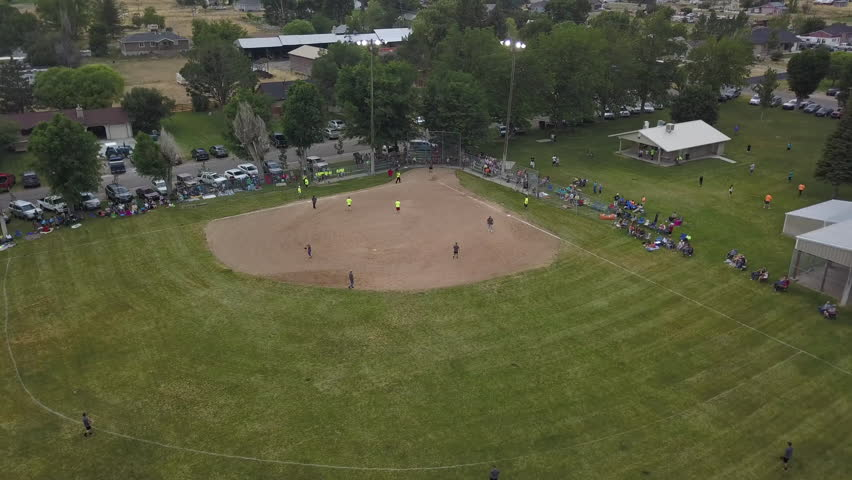 FOUNTAIN GREEN, UTAH - 14 JUL 2017: Aerial Rural town softball game evening. Small rural community play softball at all ages. From young boys and girls to seniors. Volunteers umpire. spirit teamwork