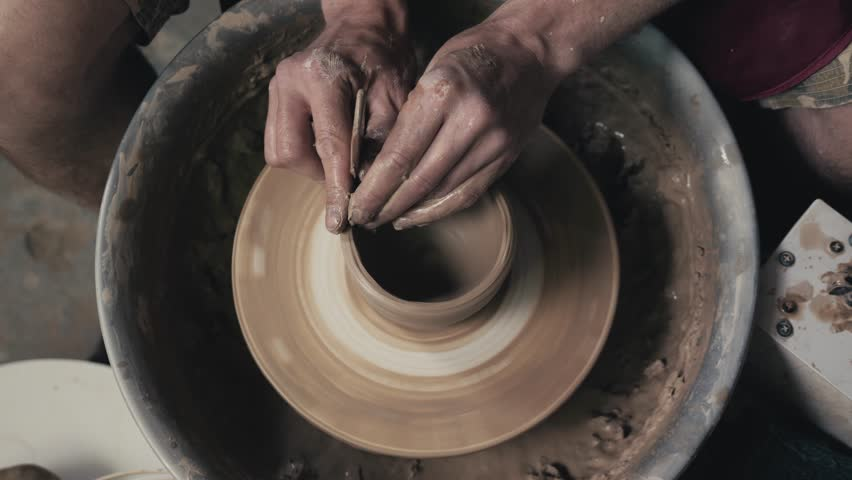 Potter shapes the clay product with pottery tools on the potter's wheel, top view, toned cinematic, craft factory authentic | Shutterstock HD Video #29228401