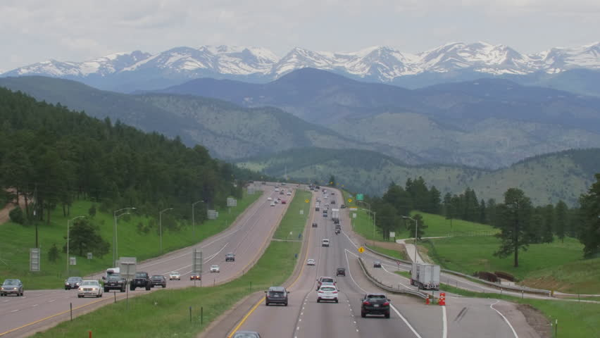 Busy traffic on Interstate Highway leading out Denver and into the rugged snowcapped Rocky Mountains of Colorado.