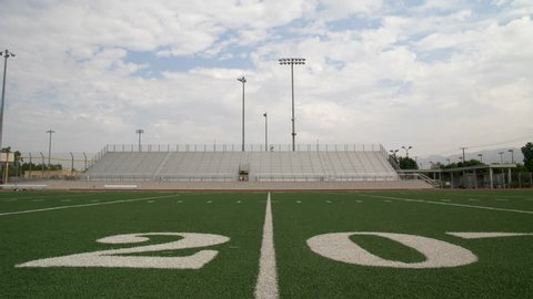 A FOOTBALL FIELD'S 20 YARD LINE.  Camera tilts down to a ground level close up of the 20 yard line on an empty football field.