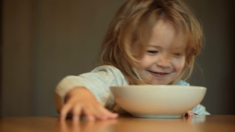 Child does not want to eat, cute child with long hair in pajamas in kitchen pushes out plate of food, breakfast or lunch. Boy is playing at the table in the morning. Nutrition and day regimen for baby