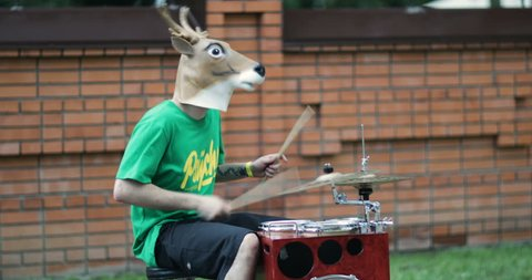 the man in the mask deer playing on the drum.deer mask.4K video
